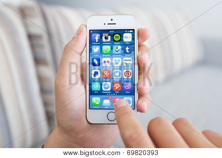 Man Holding A White Iphone 5S With Social Media Network Program On The Screen