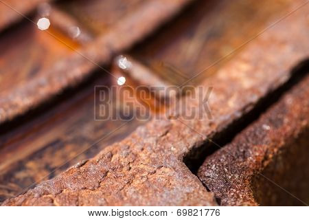 Close Up Of The Rusty Metal Manhole Cover With Water