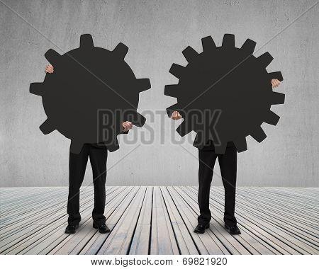 Businessmen Hold Their Different Gear On Wooden Floor