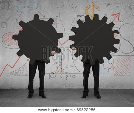 Two Businessmen Holding Different Gear With Doodles Wall
