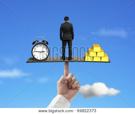 Standing Person Between Clock And Gold Balancing On Finger Seesaw