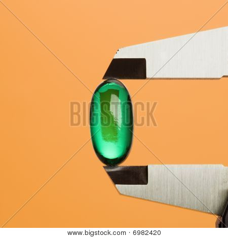 Green Capsule In Caliper. Isolated