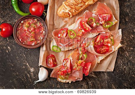 Sandwiches with ham and tomato salsa dip on a wooden background