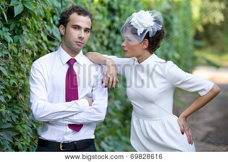 Wedding. Bride in stylish sheath dress with a hat with a veil looks at the groom.