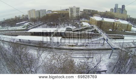 MOSCOW, RUSSIA - NOVEMBER 27, 2013: Snow-covered railway platform with a pedestrian bridge in the city, aerial view