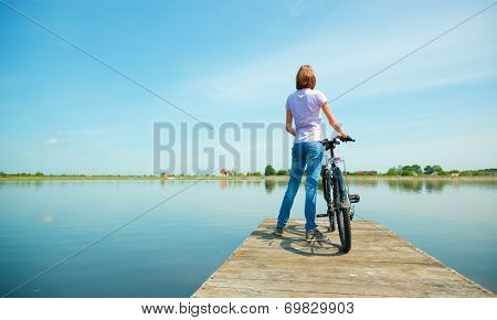 Young woman is looking at horizon standing on pier with bicycle, outdoor shoot