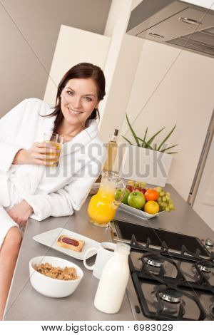 Young Woman Having Breakfast In Modern Kitchen