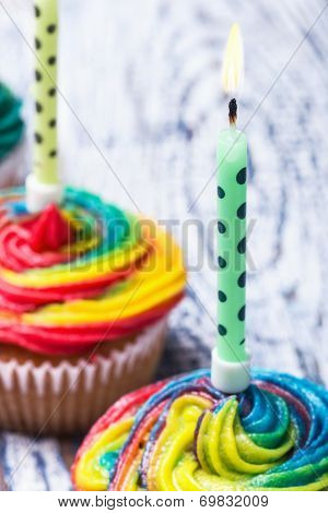 Burning Candle On Colorful Cupcakes With Cream