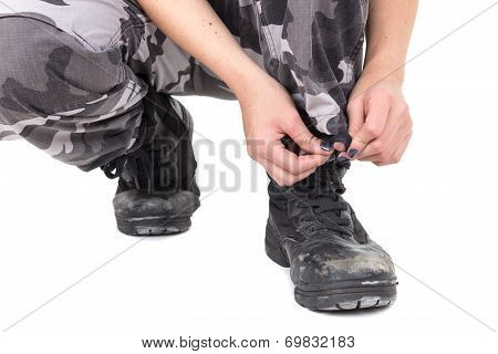 Closeup of military young woman tying her boots