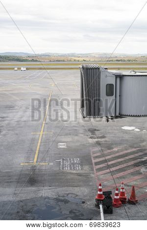 Unmanned jet bridge with empty airport landing area in the background.
