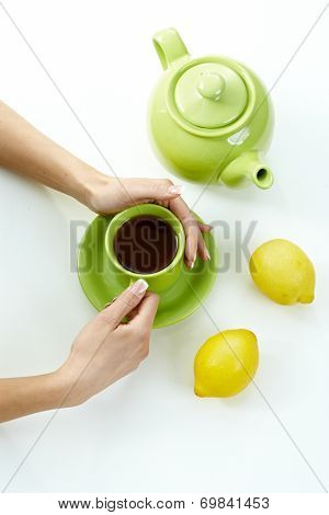 Female hand holding tea cup with kettle lemon high angle, high key. Pastel colors, white background.