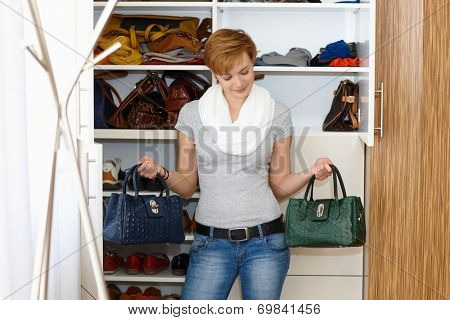 Young woman standing front of wardrobe, unable to decide which bag to take.