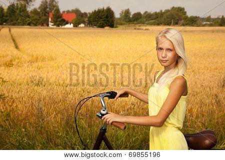 Young girl with a bike on the wheat field background.
