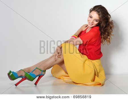 Young woman sitting on the floor, isolated in white background