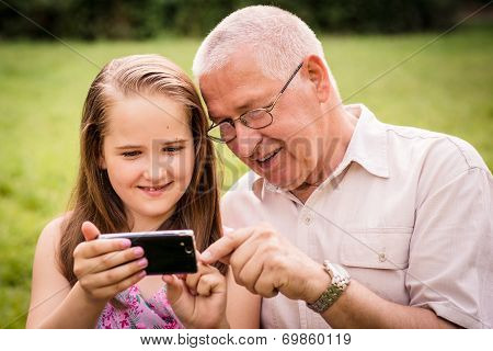Grandchild shows grandfather smartphone