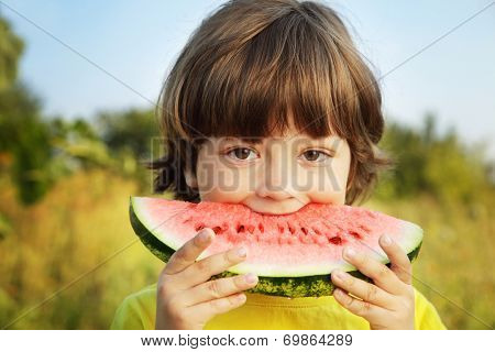 happy child eating watermelon in the garden