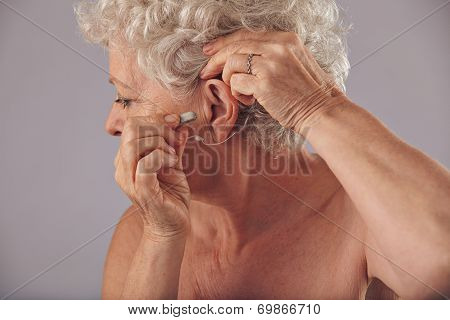 Mature Woman Inserting A Hearing Aid In Her Ear