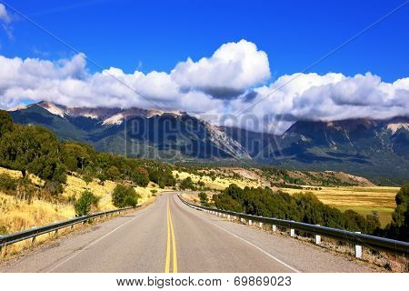 The longest road the Ruta 40 passes in Argentina among fields. The picturesque mountain chain of the Southern Andes decorates a landscape.  Patagonia