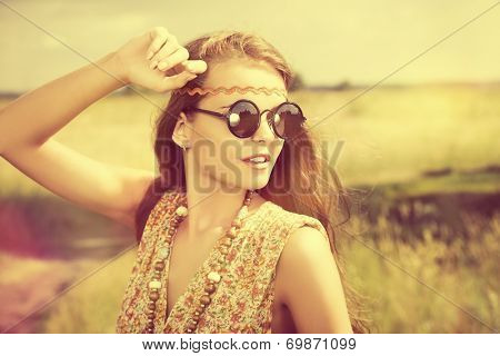 Romantic hippie girl standing in a field. Summer. Hippie style.