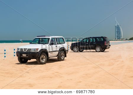 DUBAI, UAE - 2 APRIL 2014: Cars parked at the Jumeirah Beach in Dubai, UAE. Jumeirah Beach is a white sand beach that is located and named after the Jumeirah district of Dubai.