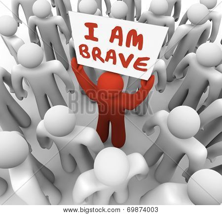 I Am Brave words on a sign held by one man in a crowd showing he is unique and different in being bold, daring, courageous and confident