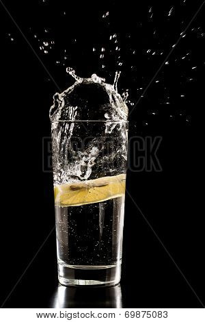 Slice Of Lemon Splashing Into A Glass Of Water
