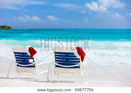 Two sun loungers with Santa hats on beautiful tropical beach with white sand and turquoise water, perfect Christmas vacation