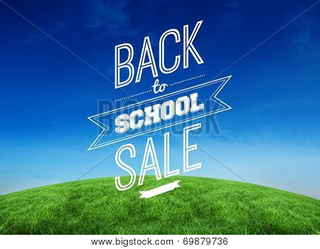 Back to school sale message against green hill under blue sky