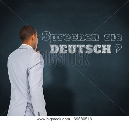 Thinking businessman against blue chalkboard, Do you speak German?