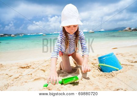 Adorable little girl wearing sun protection rash guard at beach during summer vacation