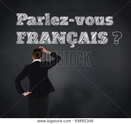 Young businesswoman standing and thinking against blackboard, Do you speak French?