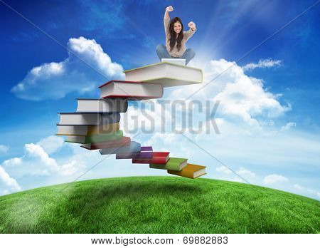 Woman looks straight ahead as she celebrates in front of her laptop against green hill under blue sky