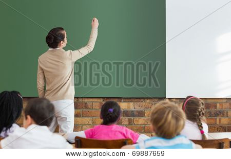 Pupils listening to their teacher at chalkboard at the elementary school