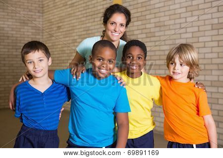 Cute pupils smiling at camera with PE teacher at the elementary school