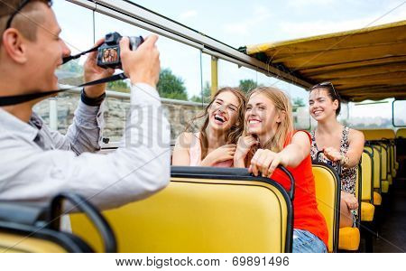 friendship, travel, vacation, summer and people concept - laughing friends with camera traveling by tour bus
