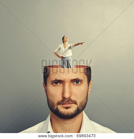 displeased businessman with open head. young smiley businesswoman standing into his head and showing the direction. photo over grey background