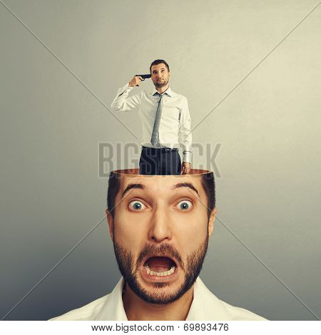 small sad man with gun standing in the head of shocked man. photo over grey background