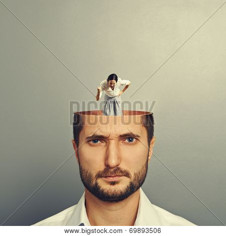 displeased man listening small angry screaming woman in his head. photo over grey background