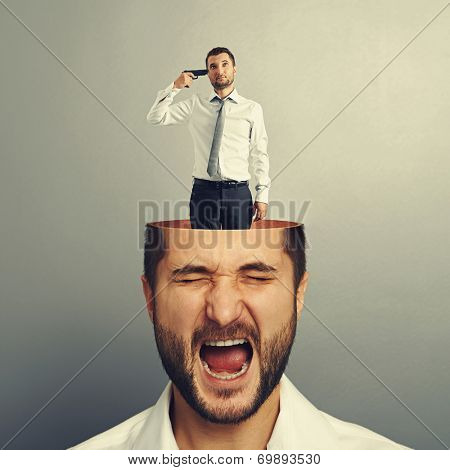 sad businessman with gun standing into the head of stressed screaming man. photo over grey background