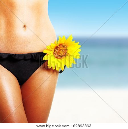 Perfect tanned woman with sunflower against sea beach.