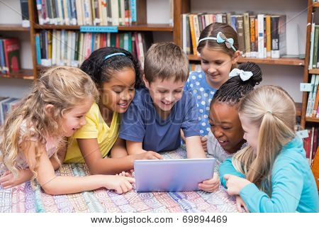 Cute pupils looking at tablet in library at the elementary school