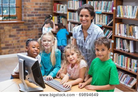 Cute pupils and teacher looking at computer in library at the elementary school