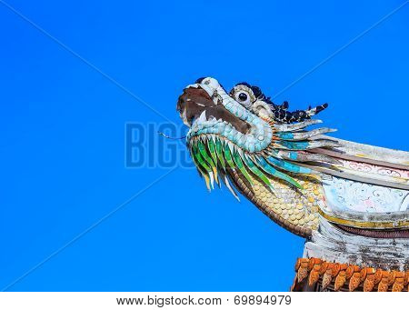 A dragon statue on the roof of a Chinese temple