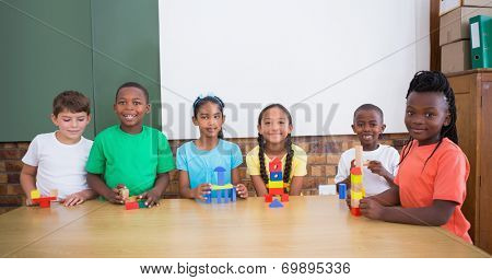 Cute pupils playing with building blocks at the elementary school