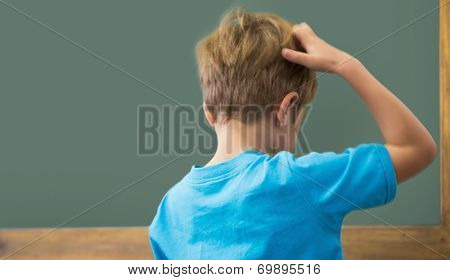 Thinking pupil scratching his head in classroom at the elementary school
