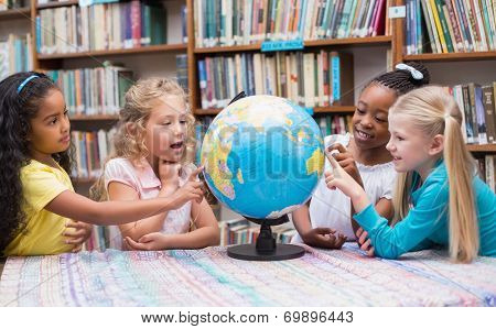 Cute pupils looking at globe in library at the elementary school