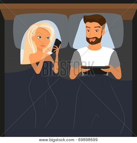 Happy couple using digital devices in bed at night
