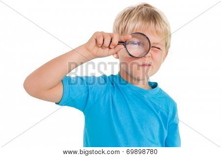 Cute little boy looking through magnifying glass on white background