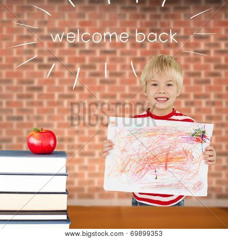 The word welcome back and cute boy showing his art against red apple on pile of books