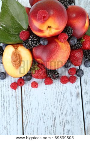 Peaches with berries on wooden table close-up